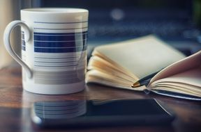 a cup of coffee near the smartphone and books