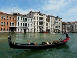 man with paddle in gondola on grand canal at june, italy, venice