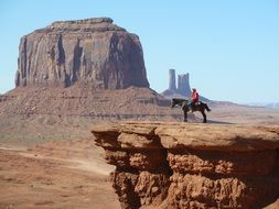 cowboy on black horse in monument valley, usa, utah