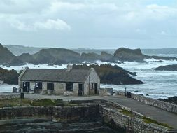 old stone building on rocky coast at stormy weather