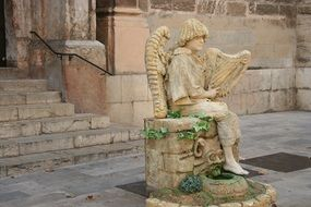 man with harp sits on antique fountain, sculpture