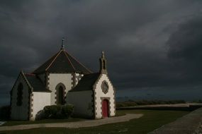 small white church building under dark stormy clouds