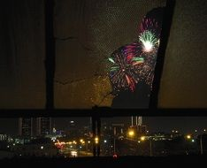 view of fireworks above city through broken window, usa, texas, fort worth