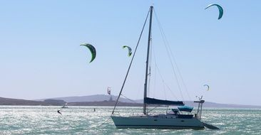paragliders at sailing boat on sea, south africa, cape town