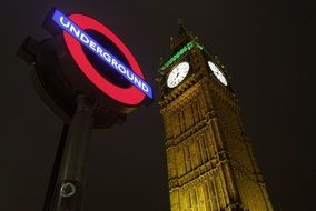 London Underground sign and Big Ben in London by night