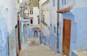 stairs down on narrow street at blue houses in old town, morocco