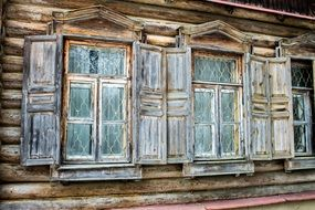 grated windows with shutters on facade of old wooden house, russia, abramtzevo