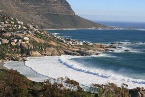 foamy ocean waves at rocky coast, south africa, cape town