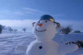 happy snowman with carrot nose and pot on head in winter landscape