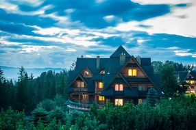 wooden cottage in forest on mountain at dusk