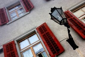 vintage lantern at window with red shutters