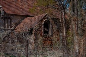 abandoned damaged stone building with red tiled roof
