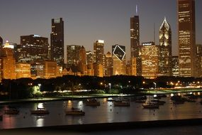 night downtown skyline with boats on lake at front, usa, illinois, chicago