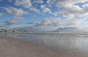 distant view of table mountain from beautiful ocean beach, south africa, cape town