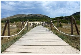 wooden rope fenced walk path through dunes, spain, mallorca