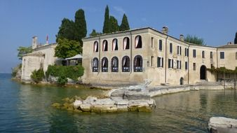old stone building on water, italy, garda