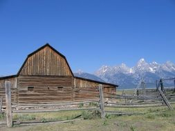 fenced old wooden barn on ranch in view of mountains, usa, wyoming