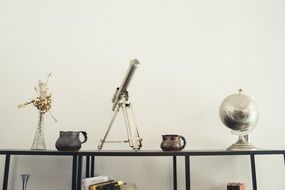 telescope, globe and vase on shelf, house deco