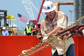 oil rig worker with hand tool at chains