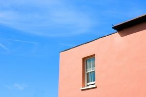 edge of pink house facade at blue sky