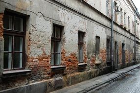 old brick building with damaged plaster on facade, poland