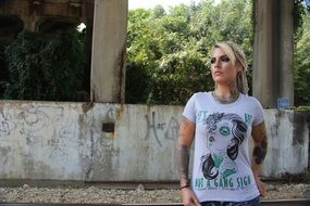 tattoo piercing makeup blond woman white shirt concrete structures
