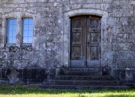 old closed wooden door above steps on stone facade