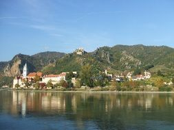 old town with church at danube river on mountain side, austria, wachau