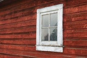 white window on red weathered wooden wall