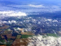 aerial view of fields at countryside through clouds