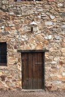 closed old wooden door in stone wall