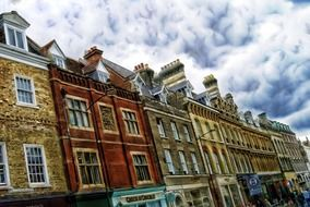 row of colorful old brick buildings at cloudy sky, uk, england, cambridge