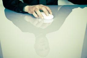 computer mouse in man's hand on desk
