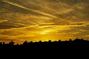 golden sunset sky above dark houses silhouettes, england