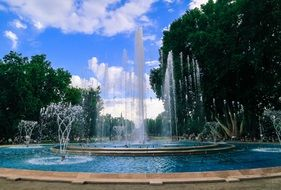 fountain with water splashes in summer park, hungary, budapest