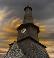 old church tower with clock and twisted spire at sunset sky