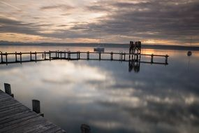 wooden pier on ammersee lake at sunset, germany, bavaria