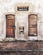 two old wooden closed doors on stone facade, italy, tuscany