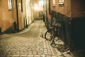 bicycle at wall on cobblestone pavement of old narrow street