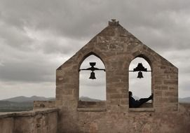 person sitting on old bell tower at cloudy sky, spain, mallorca