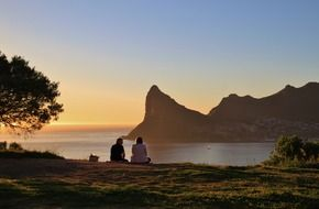 couple sitting on beautiful coast at sunset, south africa, cape town