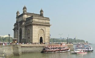 boats and tourists at gateway of india monument, mumbai
