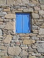 blue window on a stone wall