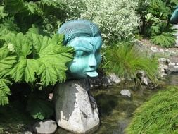 human head with long tongue, garden sculpture among plants