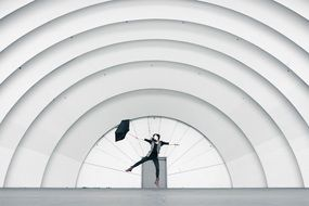 jumping girl with umbrella at arched construction