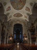 painted ceiling, benches and altar in church interior, germany