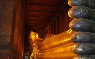 golden lying down statue, reclining buddha, in temple