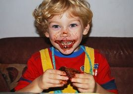 happy child boy eating chocolate muffin