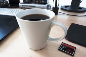 coffee cup and memory card on desk