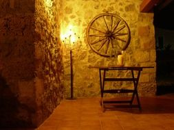 romantic interior with wooden wheel on stone wall and torch in corner, spain, mallorca